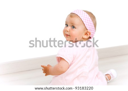Blue eyed baby girl wearing a pink dress and pink head band sitting on the floor.