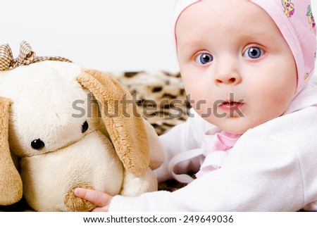 blue-eyed baby with a soft toy. studio photo. wonder - stock photo
