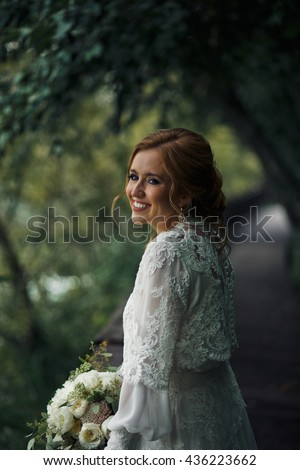 Blue-eyed bride smiles broad leaning on the fence in the garden - stock photo