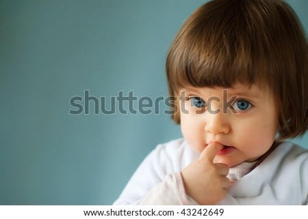 blue eyed child portrait with finger in mouth on blue background - stock photo