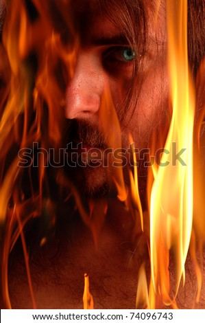Blue eyed demon in flames - stock photo