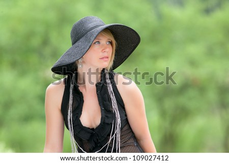 Blue-eyed girl with a hat on a green background