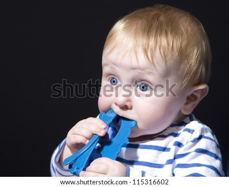 Blue eyed infant boy chewing on toy isolated against black background - stock photo