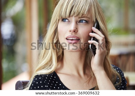 Blue eyed young blond woman on Smartphone