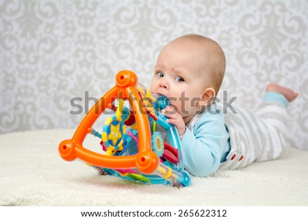 Blue eyes baby laying on belly  on soft surface and biting a colorful toy looking at the camera - stock photo