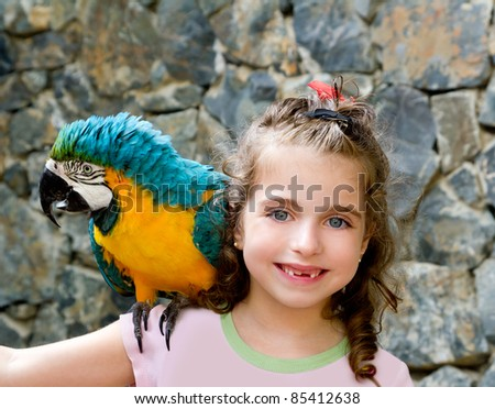 blue eyes child girl with yellow parrot in her shoulder - stock photo