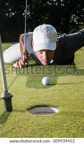 Blue eyes golfer lying down on the green, hands on the ground, checking the line of putt of his ball. Wide angle view with the flag pole on the foreground and a beautiful forest in the background - stock photo
