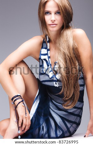 blue eyes long hair blond model in elegant dress, studio shot