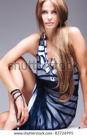 blue eyes long hair blond model in elegant dress, studio shot - stock photo