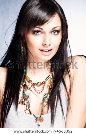 blue eyes young woman with black straight hair wearing colorful necklace with lot of pendants, small amount of grain added - stock photo