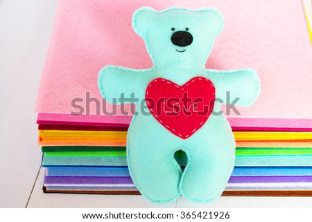 Blue felt bear toy with red heart  - stock photo