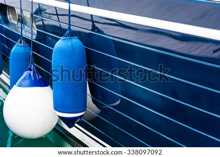 blue fenders on a boat - stock photo
