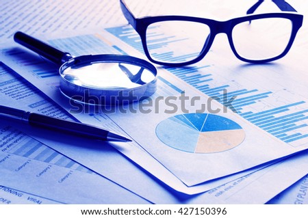 Blue filter effects images of pen glasses and magnifying on financial graph chart.For business concept. - stock photo