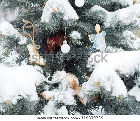 Blue fir-tree is decorated by Christmas toys. Elephants, angel, ball and scates. Christmas decoration in nature. Daylight, snowing winter.