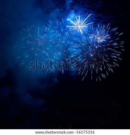 Blue fireworks on the black sky background - stock photo