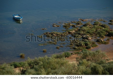 Blue fishing boat stranded in the low tide of a lake, Cacela Velha in the Algarve, south-coast of Portugal. - stock photo