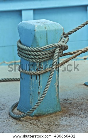 Blue fishing boat, tied to land by a rope