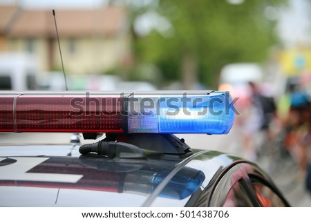 blue flashing lights of the police car at a sports event in the city