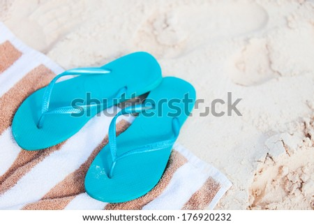 Blue flip flops at tropical beach - stock photo