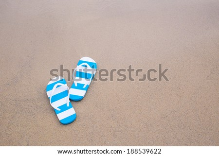Blue flip-flops on the Sand beach with copy space - stock photo