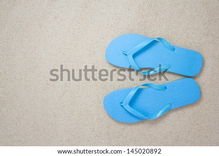 blue flip flops on the white beach sand with copyspace - stock photo