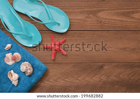 Blue Flip-flops with red starfish and towel on wooden background, top view - stock photo
