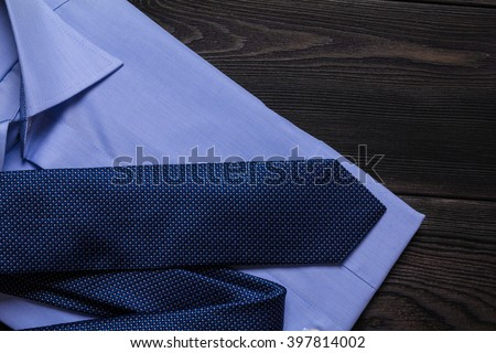 Blue folded shirt and blue necktie on black wooden table. Close up photo - stock photo