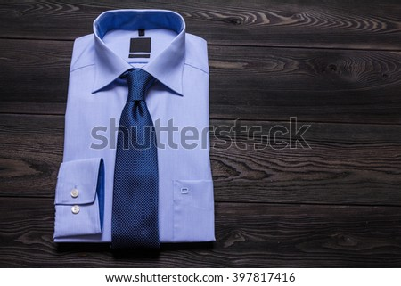 Blue folded shirt and blue necktie on black wooden table. Close up photo with copy space - stock photo