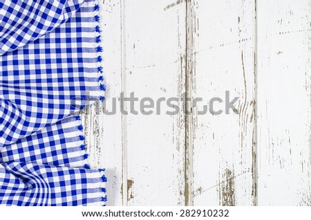 Blue folded tablecloth over wooden table - stock photo