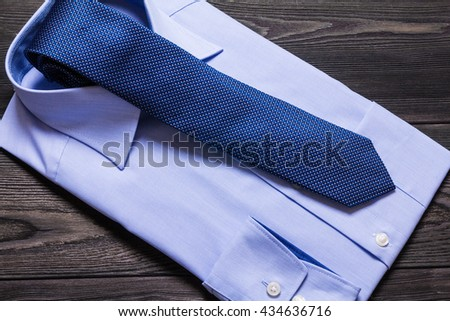 Blue formal shirt and necktie on brown wooden table - stock photo