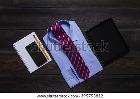 blue formal shirt, red necktie, tablet computer, smartphone, spring notebook on black wooden table