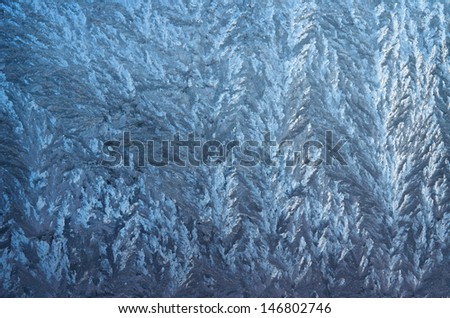 blue frozen glass covered with patterns, shot as background
