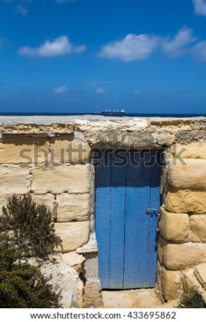 Blue gate, blue horizon and a sky Low building made of stones with a blue wooden gate, matching color with the Mediterranean sea in the background and a sky. Big ship on the horizon. - stock photo