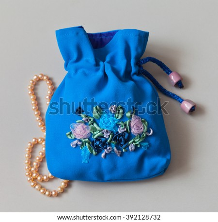 Blue gift bag for jewelry with hand-embroidered of satin ribbons and pink pearls - stock photo