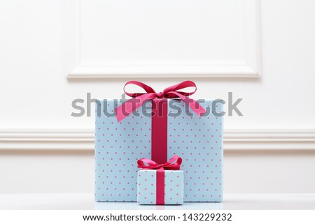 blue gift box on white table. Different sizes of the same shape gift box. A small gift box with a big gift box.  - stock photo