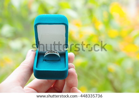 Blue gift box with ring in hand on background of greenery. Selective focus, toned image, film effect, macro, close-up - stock photo