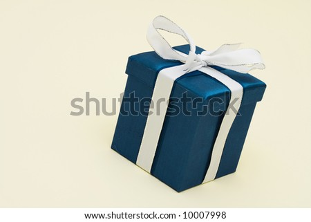 Blue gift on beige background with copy space