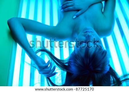 blue girl sunbathing in a solarium - stock photo