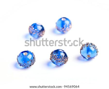 Blue glass beads closeup on white background - stock photo