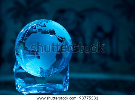 Blue glass globe and a depicted african scape in the background - stock photo