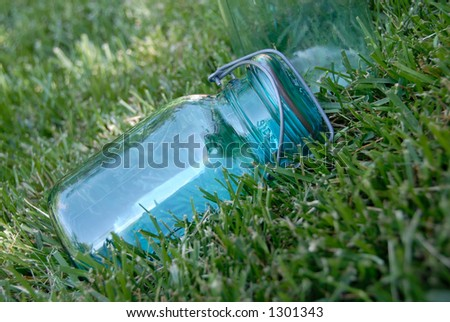 Blue glass jar, used for canning fruits and vegetables, lying in the grass. - stock photo