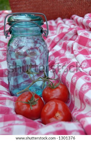 Blue glass jar with a wire holding the lid and rubber ring onto it, used for canning fruits and vegetables, sitting on a vintage table cloth.  Three tomatoes on the vine are sitting near the jar. - stock photo