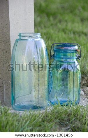 Blue glass jar with a wire holding the lid and rubber ring onto it, used for canning fruits and vegetables, sitting in the grass. - stock photo