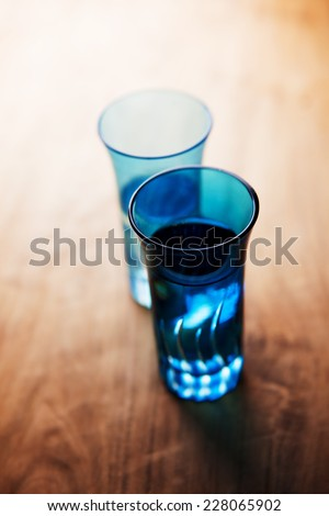 Blue glass with drink on a dim counter, with directional light.  - stock photo