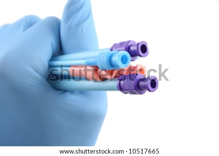blue gloved hand holding six colored surgical introducers - stock photo