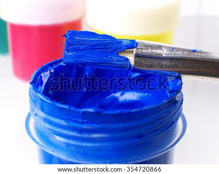 blue gouache in jar and paint brush macro, shallow depth of field - stock photo