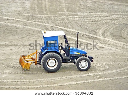 blue grader tractor waiting to clean the beach sand - stock photo
