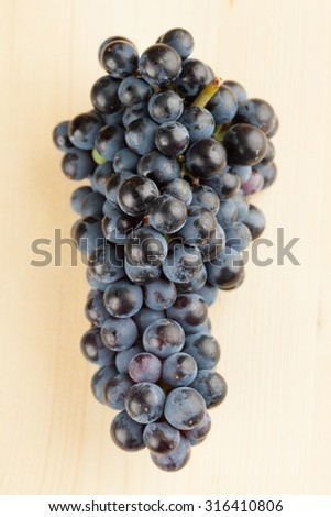 Blue grape cluster on wooden background. Shallow dof - stock photo