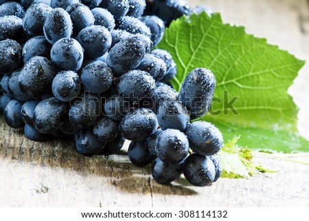 Blue grapes with leaves on old wooden background, selective focus - stock photo