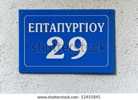 Blue greek street sign on wall - stock photo